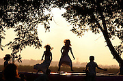 silhouette of children aged 5 to 6 playing outside at dusk