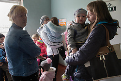 Anzhela Kovshechenko, 24, (r) waits with her son,18 month-old son, Nikita,, for an appointment with an MSF paediatrician during a mobile clinic set up in the polyclinic of the Lugansk suburb of Bolshaya Vergunka.