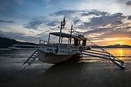 At sunset, a boat sits on the sand at low tide in Port Barton, Palawan, Philippines (July 6, 2019)