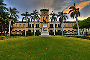 A picture of the King Kamehameha statue in front of the Ali'iolani Hale in Honolulu at dusk.