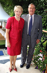 ADM.SIR JAMES & LADY PEROWNE at a garden party at the Goring Hotel, Beeston Palce, London SW1 to celebrate the unveiling of a bronze bust the late Queen Elizabeth the Queen Mother on 20th July 2004.