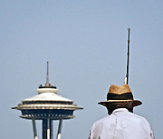 """""""uncropped original version""""<br /> 091007 LO SPACE NEEDLE AND HAT; FISHERMAN; SEA LIONS; SEACREST PARK; SKYLINE<br /> <br /> Life imitates architecture as blue skies bring a fisherman and his sun hat to Seacrest Park in West Seattle."""