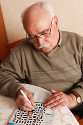Grandfather at home with a crossword,