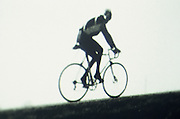 Blurry image of a man on a bicycle riding up a slight incline