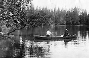 "President Calvin Coolidge (right) fishes the Brule River in Douglas County, Wisconsin, with Native American guide John LaRock in 1928. The canoe, built by local boat builder Joe Lucius, is named ""Beaver Dick"" and in the middle is Coolidge's white collie, Rob Roy."