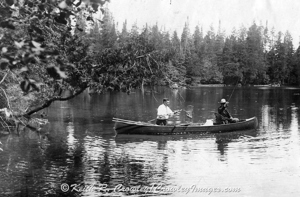 """President Calvin Coolidge (right) fishes the Brule River in Douglas County, Wisconsin, with Native American guide John LaRock in 1928. The canoe, built by local boat builder Joe Lucius, is named """"Beaver Dick"""" and in the middle is Coolidge's white collie, Rob Roy."""