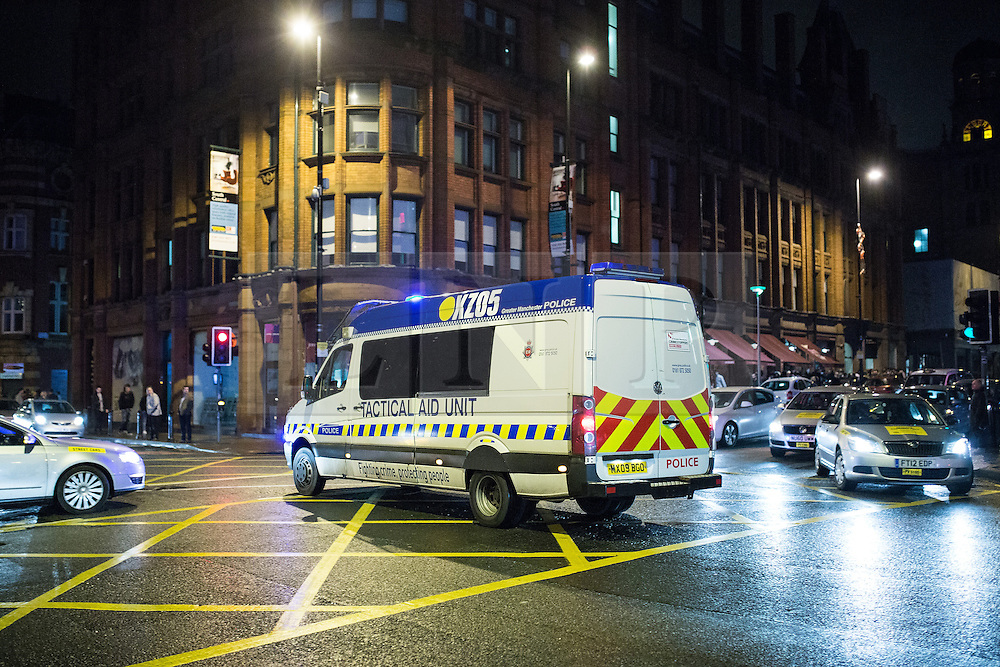 © Licensed to London News Pictures . 01/01/2015 . Manchester , UK . A police van with sirens sounding crosses through traffic on Deansgate . Revellers usher in the New Year on a night out in Manchester City Centre .  Photo credit : Joel Goodman/LNP