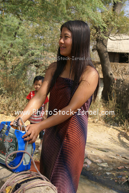 Myanmar, Pakokku, young woman draws water from a well on the banks of the Chindwin river