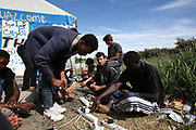Men charge their cell phones at 'the Jungle' migrant camp in Calais, France, August 10, 2015. The Calais jungle is the nickname given to a series of camps in the vicinity of Calais, France, where migrants live while they attempt to enter the United Kingdom illegally by stowing away on lorries, ferries, cars, or trains travelling through the Port of Calais or the Eurotunnel Calais Terminal. The migrants are a mix of refugees, asylum seekers and economic migrants from Darfur, Afghanistan, Syria, Iraq, Eritrea and other troubled areas of the world.