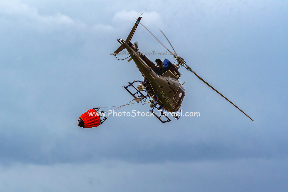 A police helicopter is used during a fire drill to airlift water to the fire zone