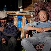 Local men relax outside simple wooden Mongolian cabin (Khangil Nuur, Mongolia - Sep. 2008) (Image ID: 080915-0825481a)