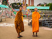 25 APRIL 2014 -  CHIANG SAEN, CHIANG RAI, THAILAND: Buddhist monks walk along the waterfront in the Golden Triangle on the Mekong River north of Chiang Saen.    PHOTO BY JACK KURTZ