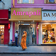 An Indian woman walks past a luxury boutique at Khan market, a posh shopping center in New Delhi