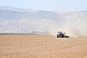 Israel, Hula Valley, Tractor ploughs and tills a field
