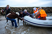 To mark the UN International Migrants Day (18th December 2020) Folkestone community members staged a Nativity scene with Jesus, Mary and Joseph arriving as refugees on the harbour beach in Folkestone, Kent, on the 12th of December 2020. As they arrived onto the beach a small group of local people welcomed them ashore with blankets and hot drinks and shelter from the rain. (photo by Andy Aitchison)