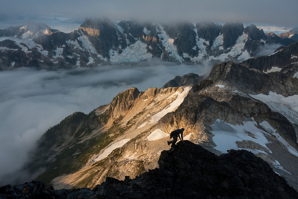 Jim Prager scrambles up the Southwest Ridge of Luna Peak (class 3) at sunrise, North Cascades National Park, Washington. The Southern Pickets are visible in the distance.