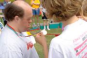 Woman admiring winning medal at award ceremony. Special Olympics U of M Bierman Athletic Complex. Minneapolis Minnesota USA