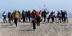 © Licensed to London News Pictures. 22/09/2021. Dungeness, UK. A young girl leads a group of mostly African migrants ashore at Dungeness in Kent after being rescued by the RNLI as they crossed the English Channel. Hundreds of migrants have made the crossing in the calm weather this week. Photo credit: Sean Aidan/LNP