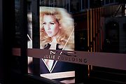 The singer, Ellie Goulding's face seen in the window of her own cosmetic brand Mac Cosmetics, in London's Carnaby Street. The pop singer has her name on the front of the shop's window and we see her face looking out with blonde hair styled in context with the shop's design concept.