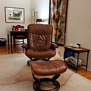 A large brown Stressless chair and footrest on a simple beige carpet with a stripe snaking through it, on a wood floor in a long room. There is a colonial style dark wooden side table and holding a white phone to the right of the chair, an empty looking box of kleenex on the bottom shelf, a large latin patterned rug hanging behind and to the right of the chair, and a colonial style wooden desk with a red fabric chair in the background. There are some diplomas near the corner of the side wall and a painting or poster of a home or small rural treet scene on the rear wall.