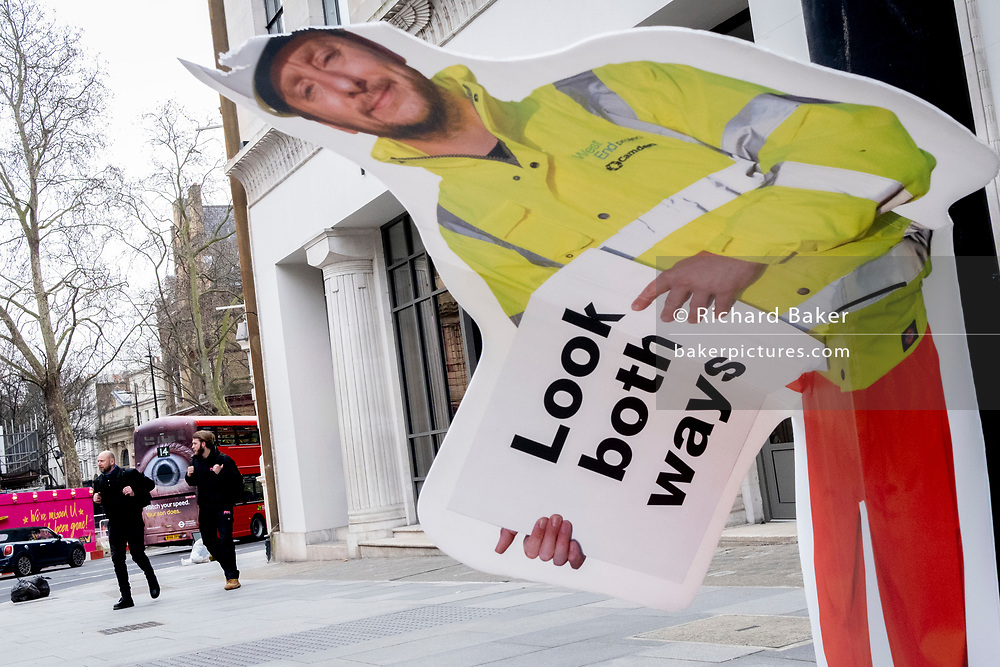 An advertising 'eye' on a London bus and a construction industry warning sign, erected to warn pedestrians, but damaged so that it is seemingly bending over at the waist, on 8th March 2021, in London, England.
