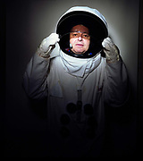 A portrait of space-suited frequent flyer astronaut Alan Watts in his north London home, England. Alan, 51, runs an electrical company and qualified for a free space space flight after being contacted by Sir Richard Branson's Virgin Galactic space company, having accumulated 2 million air miles on the Virgin Atlantic flight network. Aboard the re-usable space vehicle will be 6 passengers, each of whom will have paid $200,000 for the 40 minute flight to 360,000 feet (109.73km, or 68.18 miles) and to experience just 6 minutes of weighlessness. Flights start around 2009/10 from a Mojave desert test facility but therafter, at the new Philippe Starck-designed SpacePort America, New Mexico, USA. a 27 square mile, $225 million headquarters and mission control facility near Las Cruces.