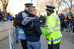 © Licensed to London News Pictures. 05/12/2016. London, UK. Police officers talk to a pro Brexit supporter who was involved in a fight with an anti Brexit supporter, outside the Supreme Court  in Westminster, London on the first day of a  Supreme Court hearing to appeal against a November 3 High Court ruling that Article 50 cannot be triggered without a vote in Parliament. Photo credit: Ben Cawthra/LNP