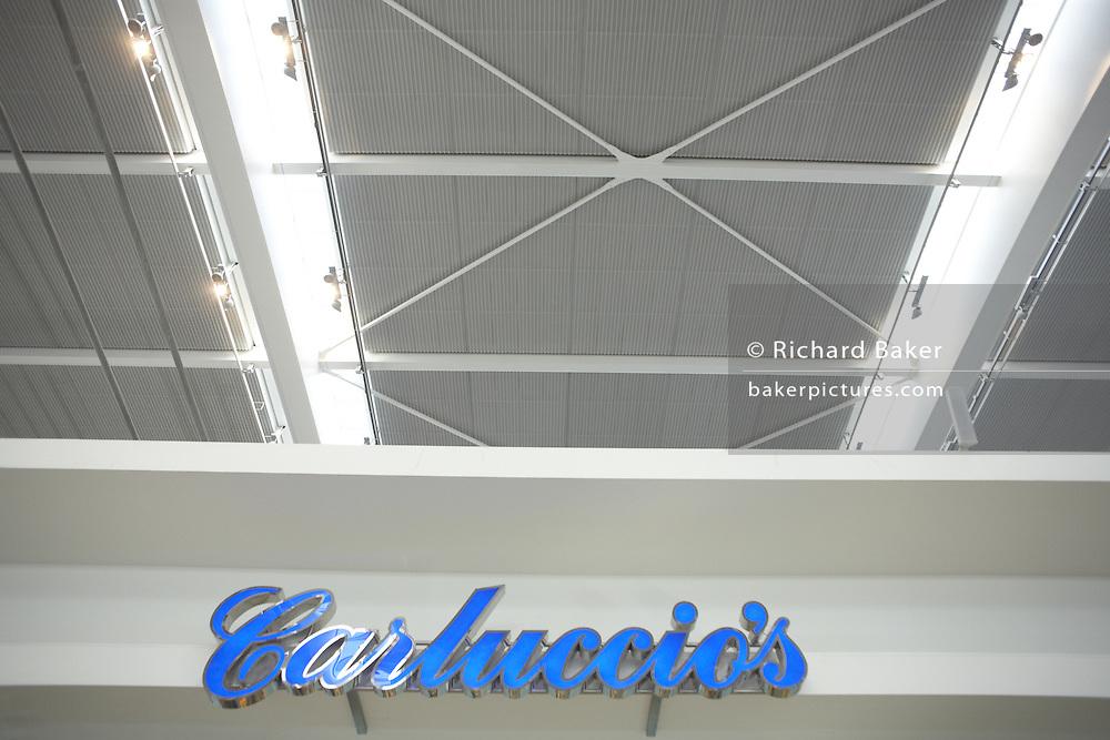 Looking upwards to Carluccio's retail sign in landside Departures area of London Heathrow Airport's Terminal 5 building