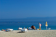 Three people on beach, with beach furniture and umbrella. Beach of Zlatni Rat, near Bol, island of Brac, Croatia