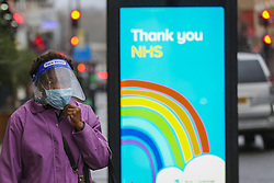 © Licensed to London News Pictures. 20/01/2021. London, UK. A woman wearing a visor and a protective face covering walks past the 'Thank you NHS' poster in north London, after the mutated variant of the SARS-Cov-2 virus continues to spread around the country. On Tuesday 19 January, 1,610 people died in the UK within 28 days of a positive Covid-19 test. This is the biggest figure reported in a single day in the UK since the pandemic began last year. According to government figures over 4.2 million people have now received the first dose of a vaccine. Photo credit: Dinendra Haria/LNP