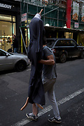 A man carries a dressed fashion mannequin wearing womens' fashion, across the road in central London, on 4th December 2017, in London England.