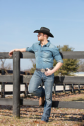 sexy cowboy leaning on a fence