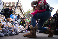 Children join demonstrators in laying teddy bears outside the gates of Downing Street in central London during a protest to highlight the high numbers of children killed in bombings in Syria and to demand the Government intervene over Russian and Syrian bombing campaigns.