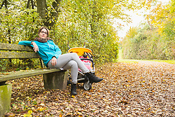 Contemplative mother sitting on bench in park by stroller