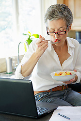 Woman Eating Fruit Salad and Using Laptop