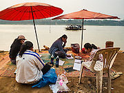 11 MARCH 2016 - LUANG PRABANG, LAOS:   Women on the bank of the Mekong River while a ferry brings people and cars across the river near Luang Prabang. Laos is one of the poorest countries in Southeast Asia. Tourism and hydroelectric dams along the rivers that run through the country are driving the legal economy.     PHOTO BY JACK KURTZ