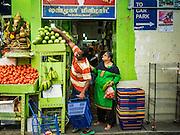 26 DECEMBER 2016 - SINGAPORE: A shop worker helps a woman buy vegetables at Tekka Market in Singapore.        PHOTO BY JACK KURTZ