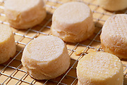 Close up photograph of a group of goat cheese buttons drying on a rack