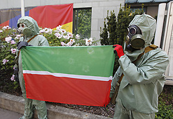 May 13, 2019 - Kiev, Kiev, Ukraine - Protesters wearing costumes of chemical protection are seen holding a flag during the demonstration..The protest due with reports of pollution of the Russian export oil 'Urals' and high content of organic chloride compounds in it and the demand to initiate an independent international audit of Russian oil production and the Russian Transneft, as well as export-oriented Russian companies Rosneft, Tatneft and Bashneft, the protest was held in front of the German Embassy due to the fact that Germany is one of the largest importers of Russian oil, according to the activists' press release (Credit Image: © Pavlo Gonchar/SOPA Images via ZUMA Wire)
