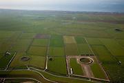 Nederland, Friesland, Gemeente Ferweradeel, 08-09-2009; zeedijk tussen de polders van het oude land en Noard-Fryslan Butendyks. Onder in beeld de zomerpolders (tegen de dijk), met verschillende dobbes (dobbe: gegraven poel met drinkwater voor het vee). Op het tweede plan de kwelders en als laatste de onbegroeide slikvelden van de kwelderwerken (landaanwinning). Noord Friesland Buitendijks is in beheer bij It Fryske Gea, maar eigendom van de Dienst der Domeinen (Rijksvastgoed- en Ontwikkelingsbedrijf, RVOB).Seawall between the old and new polders of Noard Fryslan Butendyks: first the summer polders (next to the seawall), with waterholes for drinking water (for the cattle). Next the salt marshes and finally the barren fields of mud (land reclamation). .luchtfoto (toeslag); aerial photo (additional fee required); .foto Siebe Swart / photo Siebe Swart