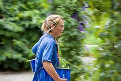 Gardener carrying basket of herbs through garden at Ballymaloe Cookery school