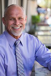 handsome bald businessman outdoors smiling
