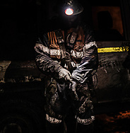 An underground worker checks his personal protection equipment (PPE)  before work