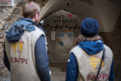 2 March 2020, Hebron: Daniel from Switzerland and Nora from Finland, both participants in the Ecumenical Accompaniment Programme in Palestine and Israel observe a wall on which 'Make love not walls' has been written. The wall has been mounted to block off the path from the Hebron Old City souq from an Israeli settlement inside the city.