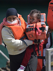 © Licensed to London News Pictures. 5/08/2021. Dover, UK. A  migrant carries a child ashore from a Border Force vessel at Dover Harbour in Kent after crossing the English Channel. Hundreds of migrants have made the crossing in recent weeks. Photo credit: Stuart Brock/LNP