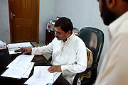SSP (Senior Superintendent of Police) Abdullah Sheikh, 42, the director of the AVCC (Anti-Violence Crime Cell) is portrayed while overlooking documents in his office in the AVCC headquarters in central Karachi, Pakistan's main economic hub.