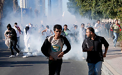 © under license to London News Pictures. 19/02/2011. Demonstrators run from tear gas fired at them by police during a march from Salmanyia Hospital Complex to Pearl Square in Manama, Bahrain today (19/02/2011). Thousands of people have returned to Bahrain's Pearl roundabout after both the army and the police leave the anti-government protest site. Photo credit should read Michael Graae/London News Pictures