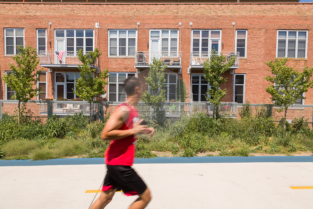 Runners along the 606 elevated bike trail, green space and park built on the old Bloomingdale Line in the Wicker Park neighborhood in Chicago, Illinois, USA