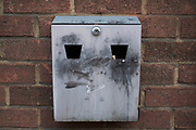 Public cigarette ashtray face attached to a brick wall in London, United Kingdom. This design of ashtrays has sprung up all over the country since the smoking band pushed smokers outside.