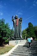 Two children walking towards statue of Grgur Ninski (Gregory of Nin), sculpted by Ivan Mestrovic. Statue is wearing a traditional red Croatian tie, or cravat.  Split, Croatia